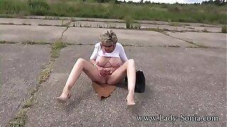 Mature blonde Lady Sonia masturbates outdoors